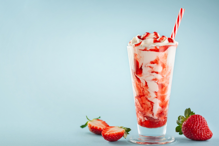 Photo for Strawberry milkshake with whipped cream and berry syrup in the tall glass on blue background. - Royalty Free Image