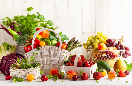 Photo pour Still life with various types of fresh vegetables, fruits and berries in baskets on a white wooden table. Concept of healthy eating. - image libre de droit