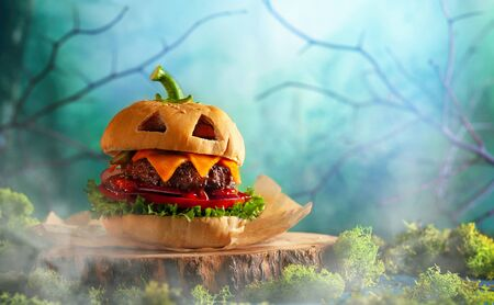 Photo pour Halloween party burger in shape of scary pumpkin  on natural wooden board. Halloween food concept. - image libre de droit