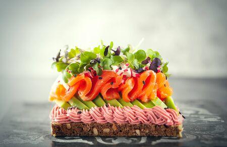 Foto de Gourmet  sandwich  with smoked salmon,avocado, beet hummus and sprouts. Concept healthy eating.  Festive appetizer. - Imagen libre de derechos