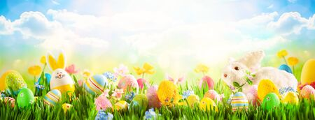 Photo pour Easter eggs, bunny and spring flowers on meadow. Easter concept. Spring or summer background with fresh grass on blue sky backdrop with copy space. - image libre de droit