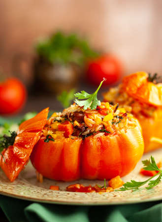 Photo for Delicious stuffed tomatoes in shape of pumpkin with rice, vegetables and meat. Concept homemade healthy eating. - Royalty Free Image
