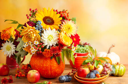 Photo for Concept of autumn festive decoration for Thanksgiving day. Autumn bouquet of flowers and berries in a pumpkin on a table, different fruits and pumpkins. - Royalty Free Image