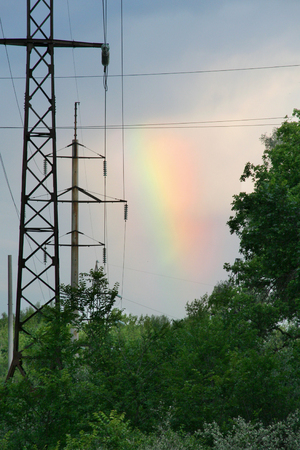 rainbow in the landscape with verdure anh high voltage posts.