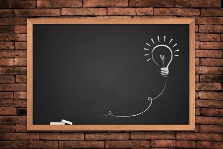 Drawing of a bulb idea blackboard on wall background