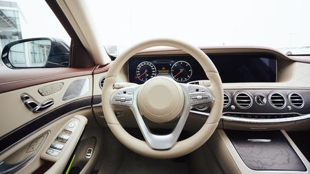 Foto de Car interior luxury. Interior of prestige modern car. Leather comfortable seats, dashboard and steering wheel. White cockpit with exclusive wood and metal decoration - Imagen libre de derechos