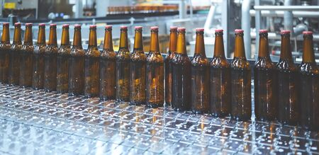 Photo for Beer bottles on the conveyor belt. Shallow dof. Selective focus. - Royalty Free Image