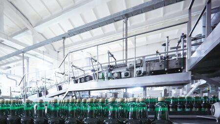 Photo pour Plastic bottles for beer or carbonated beverage moving on conveyor. Shallow DOF. Selective focus. - image libre de droit