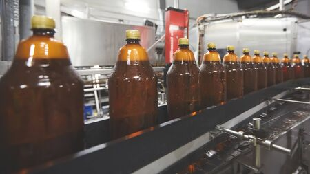 Plastic bottles for beer or carbonated beverage moving on conveyor. Shallow DOF. Selective focus.