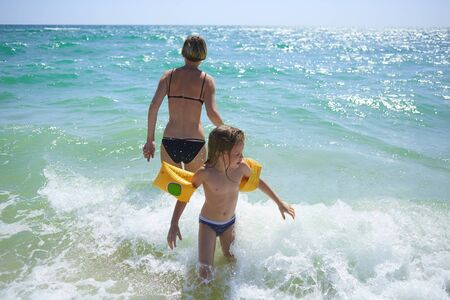 Photo pour Summer happy family of six years blonde child playing and jumping water waves embracing woman mother in sea shore beach. - image libre de droit