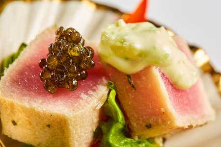 Photo pour Close up of rare seared Ahi tuna slices with fresh vegetable salad on a plate. Shallow dof - image libre de droit