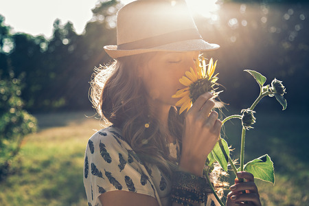 Photo pour Girl smells sunflower in nature - image libre de droit