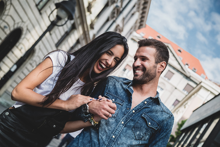 Photo pour Couple laughing and holding hands in the city - image libre de droit