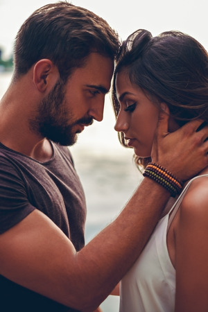 Photo pour Man is holding his girl and looking at her. They are touching with heads - image libre de droit