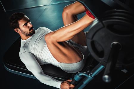 Photo pour Fit man training legs on leg press machine in the gym - image libre de droit