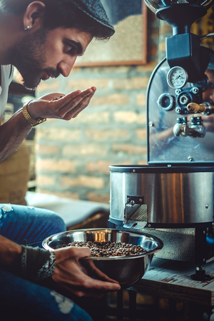 Hipster man smelling coffee beans which he roasted in a retro roasterの写真素材