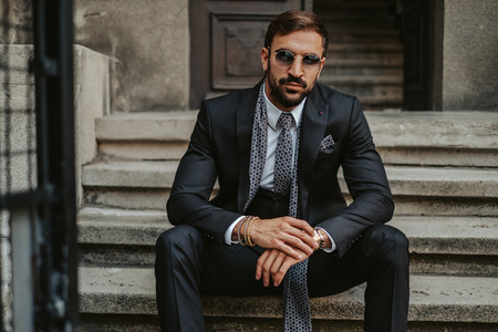 Photo pour Serious businessman sitting on the stairs and holding his watch while looking in to a camera - image libre de droit