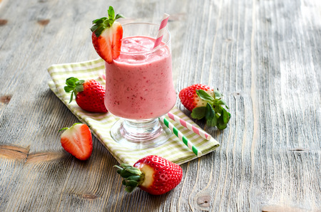 Milk shake with strawberries on wooden copy space background