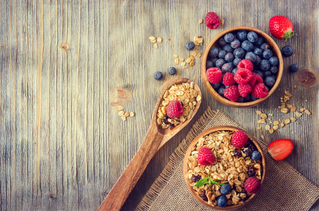 Photo pour Breakfast with fresh berries, granola or muesli on rustic wooden background, health and diet concept, copy space - image libre de droit
