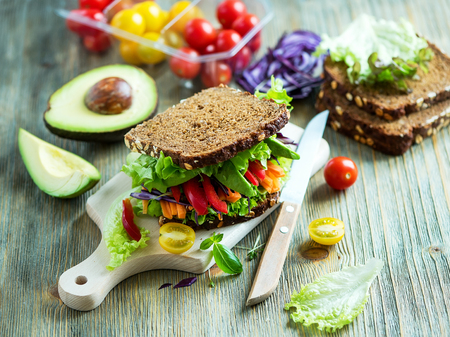 Photo for Vegan rye sandwich with fresh ingredients: avocado, salad, tomato, carrots, for healthy meal, vitamin and diet food - Royalty Free Image
