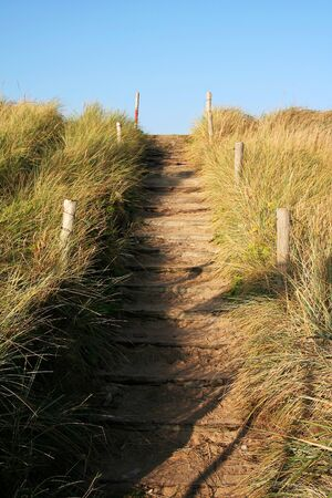 Sanded path to the beach with a blue sky