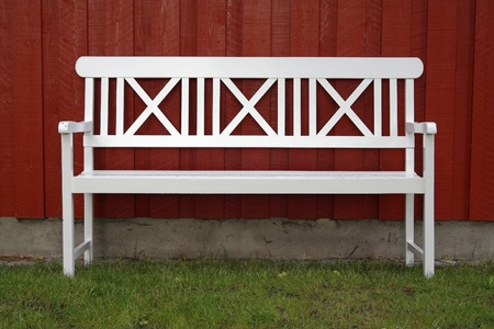 White bench in the grass in front of a red house