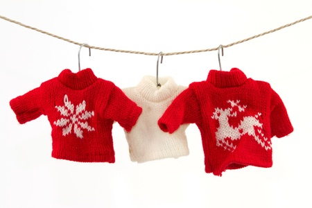 Three pullovers and a clothesline with a white background