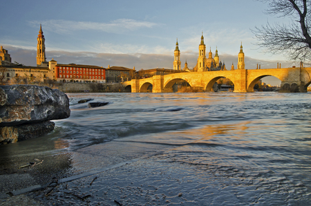 Photo pour The old stone bridge across river Ebro in Zaragoza in early morning lights of sunrise BasilicaCathedral of Our Lady of the Pillar is behind. Cathedral of the Savior is visible at the left the water flow is at background - image libre de droit