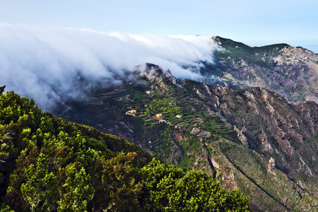 Spectacular szene of the mist coming through qui est mountains down to the valley of Anaga massif, the biosphere reserve in Tenerife Island.