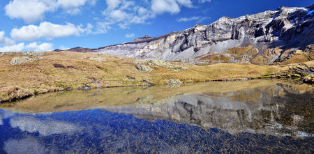Northern flank of Troumouse circus in French Pyrenees reflecting in lake water surface, with peaks, from right, Serre Mourene 3090 m, Troumouse 3085 m, Heid 3022 m, Blanc 2957 m and Gerbats peak 2904 m Midi Pyrenees, France