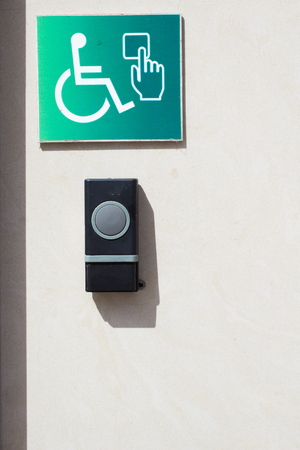 Call button for the disabled personnes. Door opener button on the wall for disabled people.