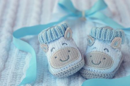 Foto de Knitted baby shoes for boy on a blue background  Greeting card  - Imagen libre de derechos