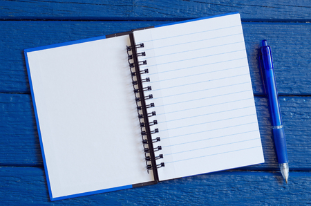 Photo for Open notepad with a pen on blue wooden table, top view. Space for your text  - Royalty Free Image
