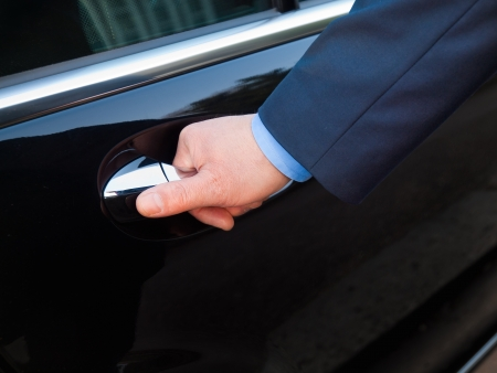 Foto de Chauffeur s hand opening passenger door  - Imagen libre de derechos