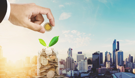 Saving money concepts, businessman hand putting coin in glass jar container, with plant bud glowing, on Bangkok city in sunrise background