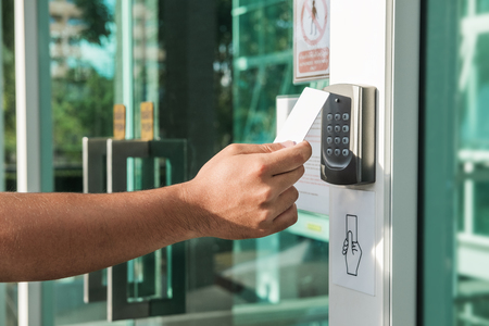 Foto de Hand using security key card scanning to open the door to entering private building. Home and building security system - Imagen libre de derechos