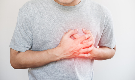 Foto de a man touching his heart, with red highlight of heart attack, and others heart disease concept, on white background - Imagen libre de derechos