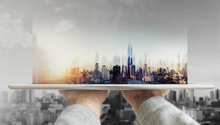 Photo pour Hand holding digital tablet with futuristic modern buildings hologram on screen - image libre de droit