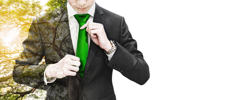 Photo pour Double exposure businessman tying green necktie and big tree with sunlight, on white background with copy space - image libre de droit