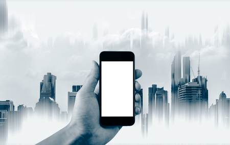 Hand holding mobile smart phone, empty white screen and abstract buildings background