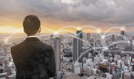 Photo pour Network technology, logistics and blockchain business. Businessman looking city view in sunset - image libre de droit