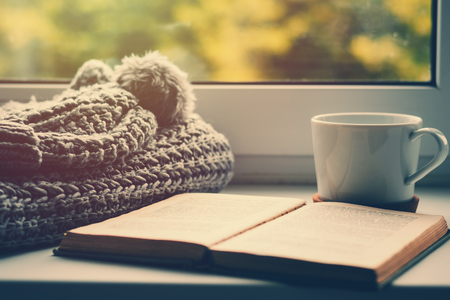 woolen scarf, cup of tea and book on the windowsill. Hygge and cozy autumn concept