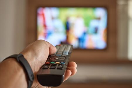 Foto de Man watching TV in the room and switches channels using remote control in his hand - Imagen libre de derechos