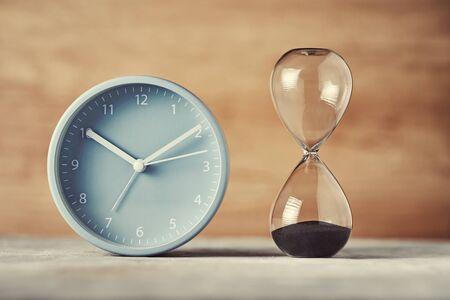 Photo pour Hourglass and alarm clock on desk, close up - image libre de droit
