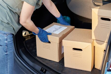 Photo for Donation and volunteering concept. Woman in gloves load box in car trunk. - Royalty Free Image