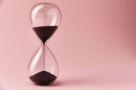 Photo pour Hourglass on pink background, close up. Urgency and running out of time concept - image libre de droit