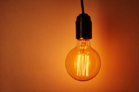 Photo for Vintage light bulb on orange background with copy space. Glowing edison bulb - Royalty Free Image