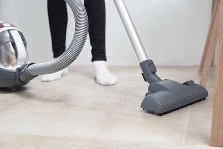 Photo pour Woman using vacuum cleaner at the floor - image libre de droit