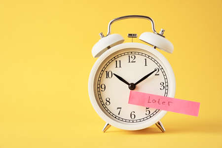 Photo pour Procrastination and delay concept. Sticky note with word later on the white alarm clock on yellow background. Urgency time - image libre de droit
