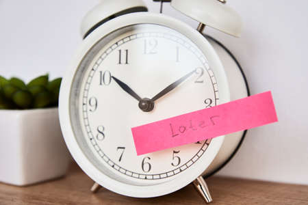 Photo pour Procrastination and delay concept. Sticky note with word later on the white alarm clock. Urgency time - image libre de droit